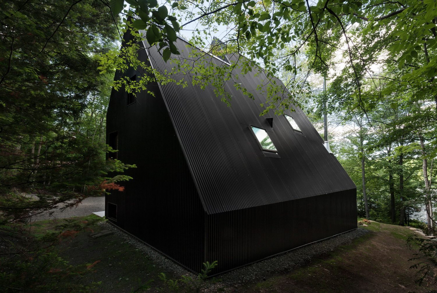 Fahouse | Black Cottage with Steep Gabled Roofs